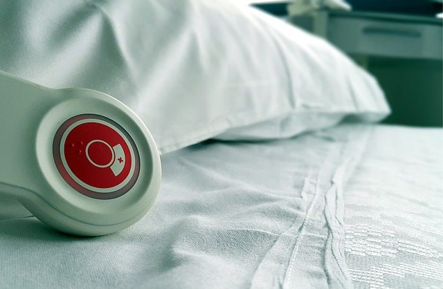 Hospital bed closeup with red call button